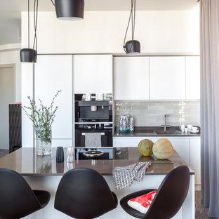 Идея дизайна: параллельная кухня среднего размера в современном стиле с плоскими фасадами, столешницей из кварцевого агломерата, бежевым фартуком, фартуком из керамической плитки, черной техникой, полом из керамогранита, островом, коричневой столешницей, накладной раковиной, серыми фасадами и серым полом