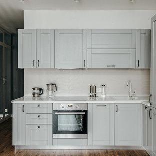 На фото: угловая кухня в скандинавском стиле с накладной раковиной, фасадами в стиле шейкер, серыми фасадами, белым фартуком, техникой из нержавеющей стали и белой столешницей с