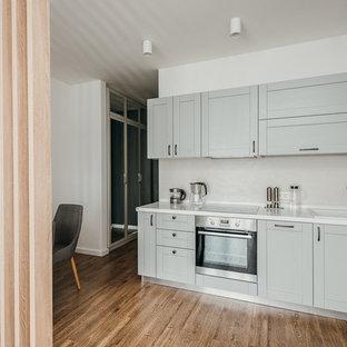 Пример оригинального дизайна: угловая кухня-гостиная в скандинавском стиле с накладной раковиной, фасадами в стиле шейкер, серыми фасадами, бежевым фартуком, техникой из нержавеющей стали, коричневым полом, белой столешницей и темным паркетным полом без острова