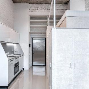 Пример оригинального дизайна: линейная кухня-гостиная в стиле лофт с плоскими фасадами, белыми фасадами, серым фартуком и черной техникой без острова