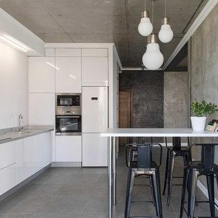 Свежая идея для дизайна: кухня среднего размера в стиле лофт с обеденным столом, плоскими фасадами, белыми фасадами, белым фартуком, техникой из нержавеющей стали, серым полом и серой столешницей - отличное фото интерьера