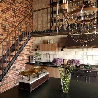 モスクワの中サイズのインダストリアルスタイルのおしゃれなI型キッチン (アンダーカウンターシンク、フラットパネル扉のキャビネット、淡色木目調キャビネット、御影石カウンター、ベージュキッチンパネル、セラミックタイルのキッチンパネル、黒い調理設備、黒いキッチンカウンター) の写真