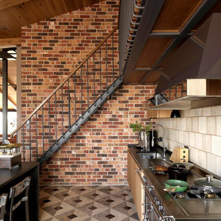 Inspiration for a mid-sized industrial single-wall eat-in kitchen in Moscow with marble floors, multi-coloured floor, an undermount sink, flat-panel cabinets, light wood cabinets, granite benchtops, beige splashback, ceramic splashback, black appliances and black benchtop.