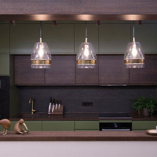 This is an example of a contemporary galley open plan kitchen in Moscow with a single-bowl sink, flat-panel cabinets, green cabinets, brown splashback and black appliances.