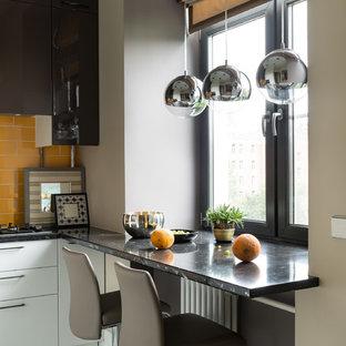 Неиссякаемый источник вдохновения для домашнего уюта: маленькая угловая кухня в современном стиле с плоскими фасадами, белыми фасадами, столешницей из акрилового камня, оранжевым фартуком, фартуком из керамической плитки, полом из керамической плитки, белым полом и черной столешницей