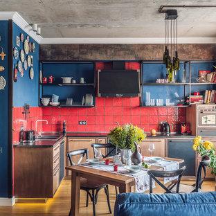 На фото: угловая кухня-гостиная в стиле лофт с накладной раковиной, плоскими фасадами, красным фартуком, черной техникой, паркетным полом среднего тона, коричневым полом, темными деревянными фасадами и фартуком из керамической плитки без острова