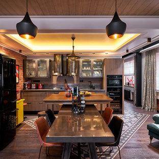 На фото: кухня-гостиная среднего размера в стиле лофт с темным паркетным полом, коричневым полом, монолитной раковиной, стеклянными фасадами, фасадами из нержавеющей стали, столешницей из нержавеющей стали, черной техникой и островом с