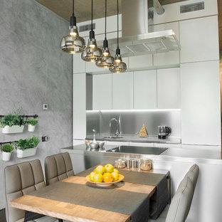 Immagine di una cucina parallela industriale di medie dimensioni con ante lisce, ante bianche, top in acciaio inossidabile, paraspruzzi a effetto metallico, paraspruzzi con piastrelle di metallo, elettrodomestici da incasso, pavimento in cemento, isola e pavimento marrone
