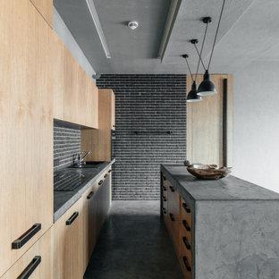 На фото: параллельные кухни в стиле лофт с накладной раковиной, плоскими фасадами, светлыми деревянными фасадами, серым фартуком, фартуком из кирпича, бетонным полом, островом, серым полом и серой столешницей