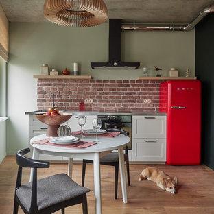 Kleine Industrial Wohnküche mit integriertem Waschbecken, Schrankfronten im Shaker-Stil, weißen Schränken, Edelstahl-Arbeitsplatte, Küchenrückwand in Rot, Rückwand aus Backstein, bunten Elektrogeräten und hellem Holzboden in Moskau