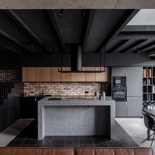 На фото: параллельная кухня-гостиная в стиле лофт с плоскими фасадами, фасадами цвета дерева среднего тона, красным фартуком, фартуком из кирпича, черной техникой, бетонным полом, островом, серым полом, серой столешницей и балками на потолке с