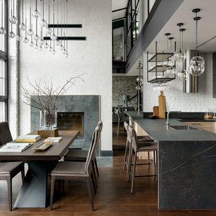 Стильный дизайн: п-образная кухня-гостиная в стиле лофт с врезной раковиной, фасадами с утопленной филенкой, светлыми деревянными фасадами, островом и черной столешницей - последний тренд