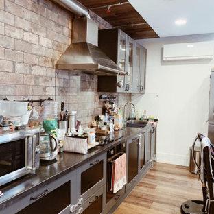 Идея дизайна: прямая кухня среднего размера в стиле лофт с монолитной раковиной, фасадами в стиле шейкер, серыми фасадами, серым фартуком, фартуком из кирпича, коричневым полом и черной столешницей без острова