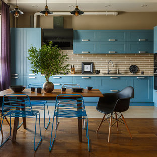Idées déco pour une cuisine américaine industrielle avec un évier posé, un placard à porte shaker, des portes de placard turquoises, une crédence beige, un électroménager noir, un sol beige et un plan de travail beige.