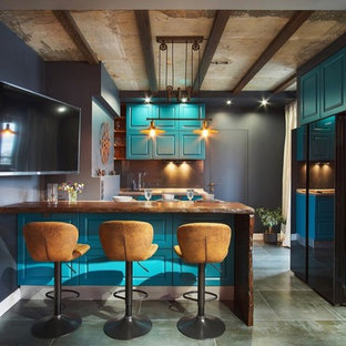 Design ideas for a small industrial galley open plan kitchen in Other with an undermount sink, raised-panel cabinets, turquoise cabinets, wood benchtops, black splashback, glass sheet splashback, black appliances, porcelain floors, with island, grey floor and brown benchtop.