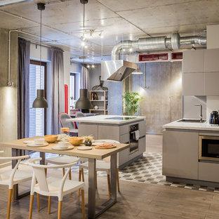 Свежая идея для дизайна: кухня-гостиная в стиле лофт с паркетным полом среднего тона, коричневым полом, накладной раковиной, плоскими фасадами, серыми фасадами, техникой из нержавеющей стали и островом - отличное фото интерьера