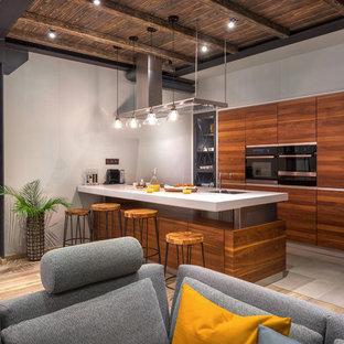 Foto på ett industriellt vit kök, med en undermonterad diskho, släta luckor, skåp i mellenmörkt trä, rostfria vitvaror, en köksö och grått golv