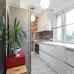 Идея дизайна: параллельная, отдельная кухня в современном стиле с плоскими фасадами, белыми фасадами, фартуком из стекла, полом из ламината и черной техникой без острова