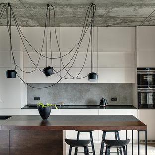 Пример оригинального дизайна: прямая кухня в стиле лофт с врезной раковиной, плоскими фасадами, белыми фасадами, серым фартуком, техникой из нержавеющей стали, островом, бежевым полом и черной столешницей