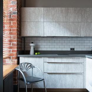 На фото: маленькая угловая кухня в стиле лофт с плоскими фасадами, серыми фасадами, белым фартуком и серой столешницей без острова
