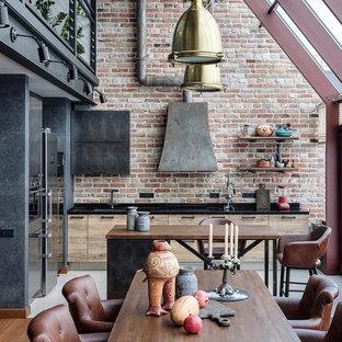 Неиссякаемый источник вдохновения для домашнего уюта: параллельная кухня в стиле лофт с обеденным столом, плоскими фасадами, фасадами цвета дерева среднего тона, красным фартуком, фартуком из кирпича, островом и черной столешницей
