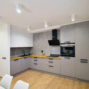 На фото: угловая кухня в современном стиле с накладной раковиной, плоскими фасадами, серыми фасадами, деревянной столешницей, серым фартуком, светлым паркетным полом, коричневым полом и коричневой столешницей