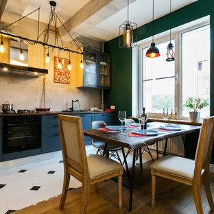 На фото: линейная кухня в стиле лофт с обеденным столом, фасадами в стиле шейкер, синими фасадами, бежевым фартуком, черной техникой и белым полом без острова с