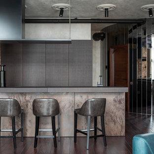 На фото: прямая кухня в стиле лофт с плоскими фасадами, черными фасадами, темным паркетным полом, полуостровом и коричневым полом