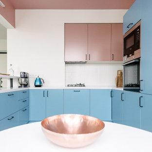 Неиссякаемый источник вдохновения для домашнего уюта: п-образная кухня среднего размера в современном стиле с обеденным столом, плоскими фасадами, синими фасадами, белым фартуком, фартуком из керамогранитной плитки, техникой из нержавеющей стали, полуостровом и белой столешницей