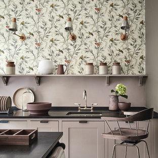 Modelo de cocina clásica renovada con fregadero bajoencimera, armarios con paneles empotrados, una isla y suelo beige
