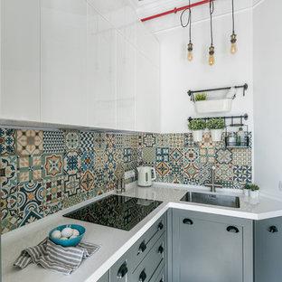 Стильный дизайн: маленькая угловая кухня в современном стиле с врезной раковиной, серыми фасадами, столешницей из акрилового камня, разноцветным фартуком, фартуком из керамической плитки, белой столешницей и фасадами с утопленной филенкой без острова - последний тренд