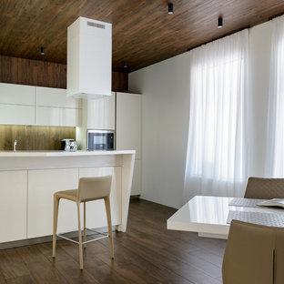 На фото: кухни в современном стиле с обеденным столом, плоскими фасадами, белыми фасадами, коричневым фартуком, фартуком с окном, темным паркетным полом, полуостровом, коричневым полом и белой столешницей