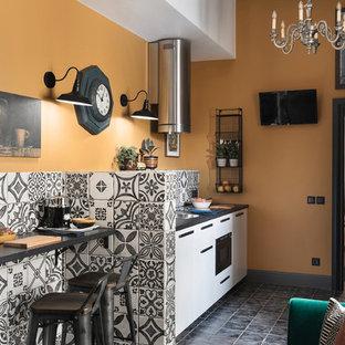 На фото: маленькая линейная кухня в средиземноморском стиле с обеденным столом, полом из керамической плитки, серым полом, накладной раковиной, плоскими фасадами, белыми фасадами, разноцветным фартуком, черной техникой и черной столешницей без острова с