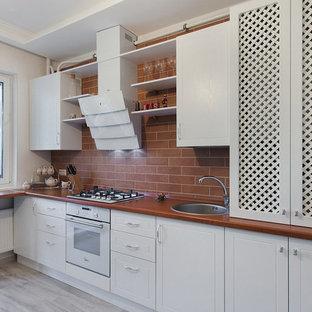 Стильный дизайн: прямая кухня в стиле современная классика с накладной раковиной, белыми фасадами, коричневым фартуком, белой техникой, коричневой столешницей, деревянной столешницей, фартуком из плитки кабанчик и полуостровом - последний тренд