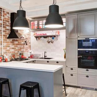 На фото: п-образная кухня в стиле современная классика с накладной раковиной, фасадами с выступающей филенкой, серыми фасадами, коричневым фартуком, фартуком из кирпича, черной техникой, полуостровом, серым полом и белой столешницей с