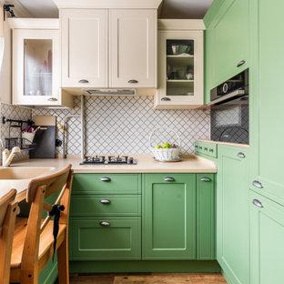 На фото: маленькая отдельная, п-образная кухня в стиле современная классика с монолитной раковиной, фасадами с утопленной филенкой, зелеными фасадами, белым фартуком, черной техникой, коричневым полом и бежевой столешницей без острова