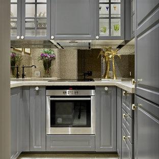 モスクワの小さいトランジショナルスタイルのおしゃれなコの字型キッチン (グレーのキャビネット、シルバーの調理設備、ベージュの床、ガラス扉のキャビネット、ミラータイルのキッチンパネル、ベージュのキッチンカウンター) の写真