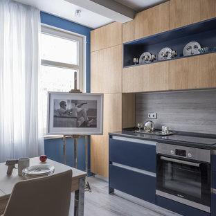 На фото: отдельная, линейная кухня в современном стиле с плоскими фасадами, синими фасадами, серым фартуком, техникой из нержавеющей стали, серым полом и черной столешницей без острова с