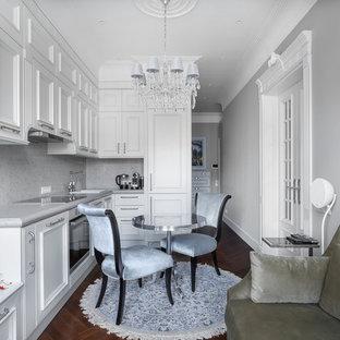 Пример оригинального дизайна: угловая кухня-гостиная в классическом стиле с накладной раковиной, фасадами с утопленной филенкой, белыми фасадами, белым фартуком, техникой из нержавеющей стали, коричневым полом и паркетным полом среднего тона без острова
