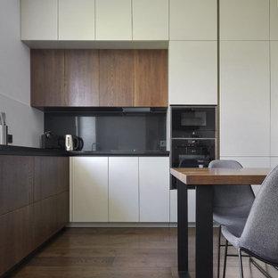 Стильный дизайн: угловая кухня среднего размера в современном стиле с обеденным столом, плоскими фасадами, фасадами цвета дерева среднего тона, черным фартуком, фартуком из стекла, техникой под мебельный фасад, коричневым полом и черной столешницей без острова - последний тренд