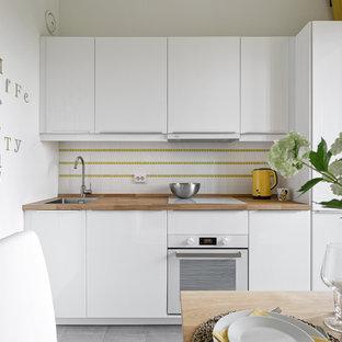 На фото: маленькая отдельная, прямая кухня в скандинавском стиле с накладной раковиной, плоскими фасадами, белыми фасадами, деревянной столешницей, белым фартуком, белой техникой, серым полом и коричневой столешницей без острова