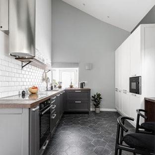 Пример оригинального дизайна: параллельная кухня-гостиная среднего размера в современном стиле с врезной раковиной, фасадами в стиле шейкер, черными фасадами, деревянной столешницей, белым фартуком, фартуком из керамической плитки, черной техникой, полом из керамогранита, серым полом и коричневой столешницей