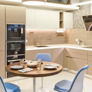 Пример оригинального дизайна интерьера: угловая кухня-гостиная в современном стиле с врезной раковиной, плоскими фасадами, бежевыми фасадами, стеклянной столешницей, серым фартуком, фартуком из керамической плитки и черной техникой без острова