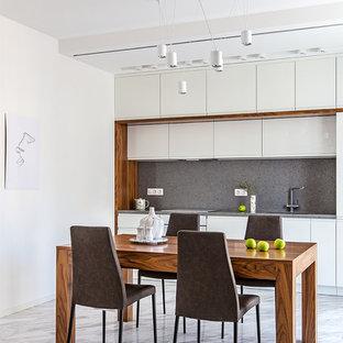 На фото: прямая кухня в современном стиле с обеденным столом, плоскими фасадами, белыми фасадами, серым фартуком, мраморным полом, белым полом и серой столешницей без острова с