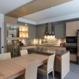 На фото: угловая кухня в современном стиле с обеденным столом, плоскими фасадами, светлыми деревянными фасадами, серым фартуком, техникой из нержавеющей стали, островом и серым полом