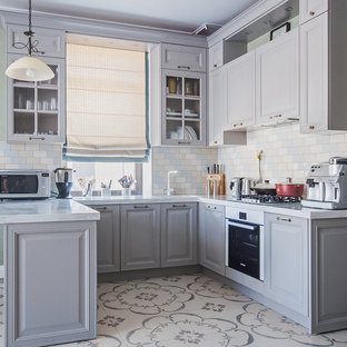 Inspiration for a mid-sized traditional u-shaped eat-in kitchen in Moscow with raised-panel cabinets, ceramic splashback, ceramic floors, grey cabinets, multi-coloured splashback, white appliances and a peninsula.