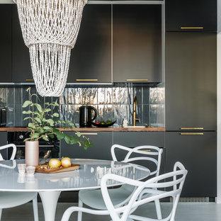 На фото: прямая кухня в современном стиле с обеденным столом, плоскими фасадами, черными фасадами, серым фартуком, черной техникой, белым полом и коричневой столешницей без острова