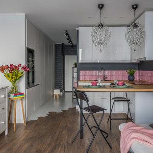 Свежая идея для дизайна: маленькая п-образная кухня в современном стиле с обеденным столом, накладной раковиной, плоскими фасадами, белыми фасадами, деревянной столешницей, розовым фартуком, фартуком из керамической плитки, техникой из нержавеющей стали, полом из ламината, полуостровом, коричневым полом и коричневой столешницей - отличное фото интерьера