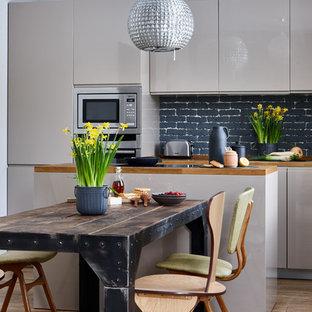Создайте стильный интерьер: линейная кухня-гостиная в стиле фьюжн с плоскими фасадами, бежевыми фасадами, столешницей из дерева, черным фартуком, фартуком из кирпича, техникой из нержавеющей стали, островом, коричневым полом и коричневой столешницей - последний тренд