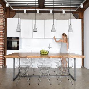 Пример оригинального дизайна: прямая кухня в стиле лофт с обеденным столом, плоскими фасадами, белыми фасадами, белым фартуком, бетонным полом, серым полом, белой столешницей, врезной раковиной и техникой под мебельный фасад без острова